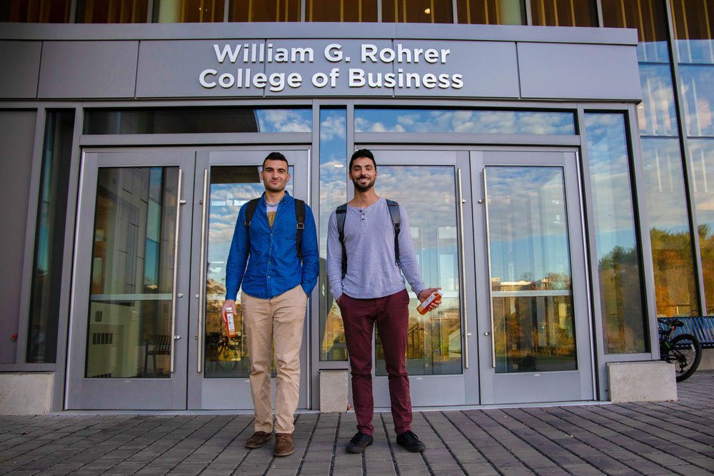 2 students standing outside of Business Hall